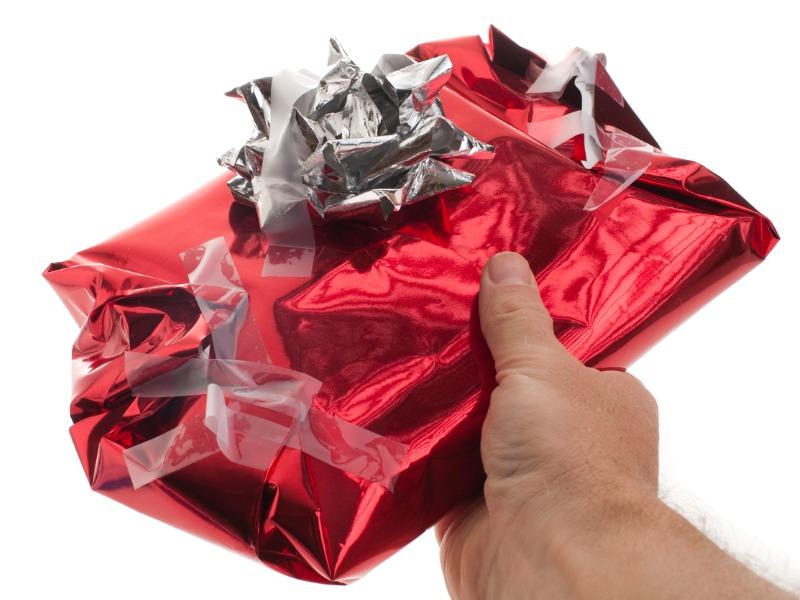 Quelqu'un qui tend un paquet cadeau mal emballé.