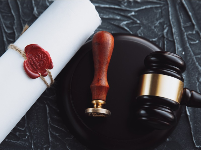 Un document papier scellé à côté d'un marteau de juge.