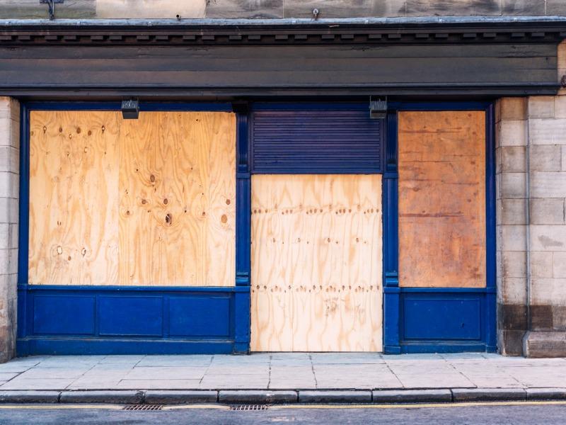 Un magasin dont les vitres ont été remplacées par du bois car il a fait faillite.