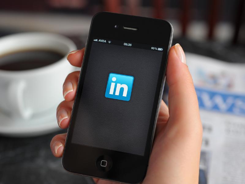 Une personne tenant son téléphone sur lequel on voit le logo de LinkedIn