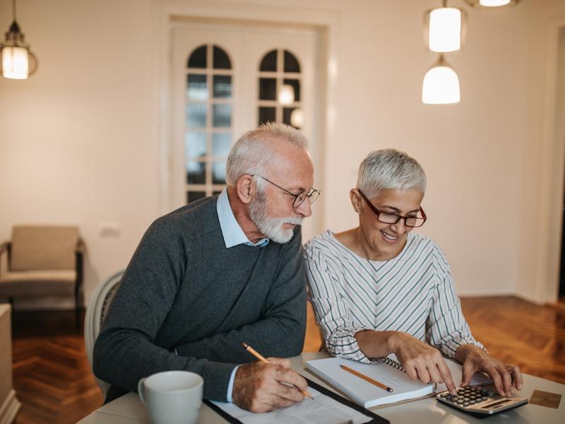 Un couple de personnes âgées avec une calculatrice et des feuilles.