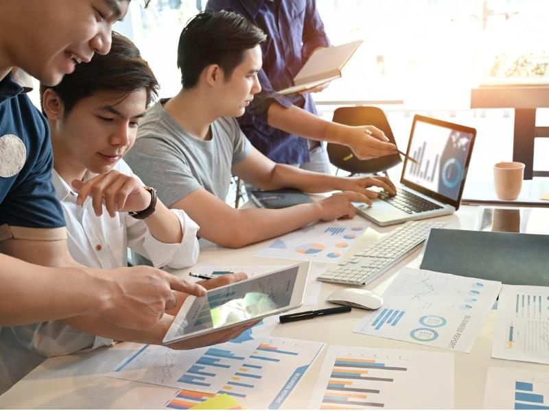 Quatre personnes d'un côté d'une table. Deux d'entre elles, montrent aux deux autres des choses sur leur ordinateur. Des graphiques sont posés sur la table.