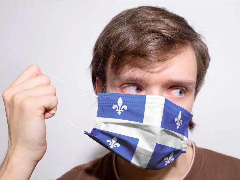 Un homme mettant un masque à l'effigie du Québec.