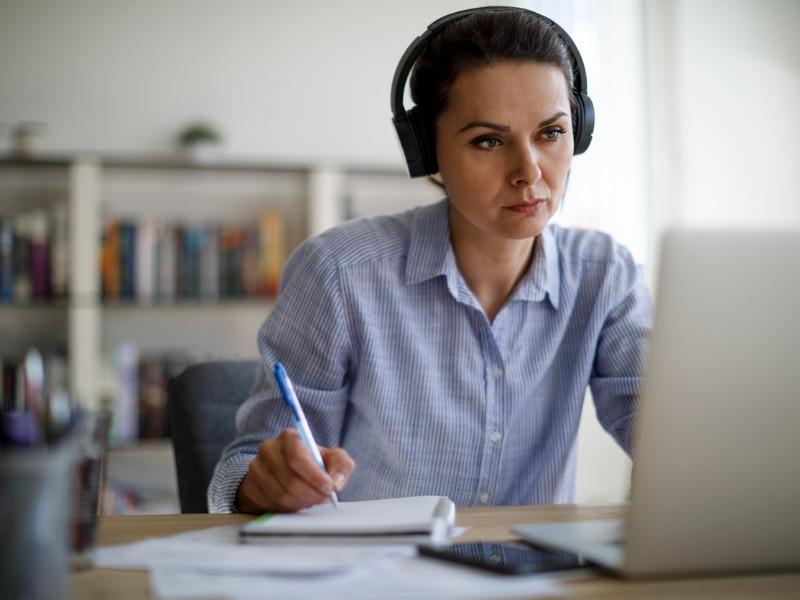 Une femme assise à un bureau devant un ordinateur. Elle porte des écouteurs et semble prendre des notes.