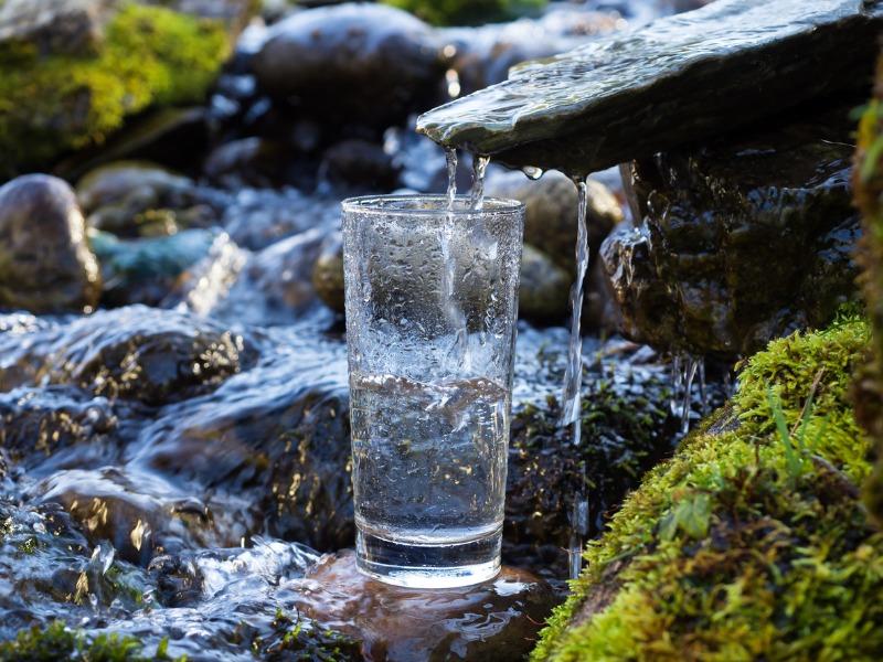 Un verre d'eau qui récolte l'eau d'une cascade.