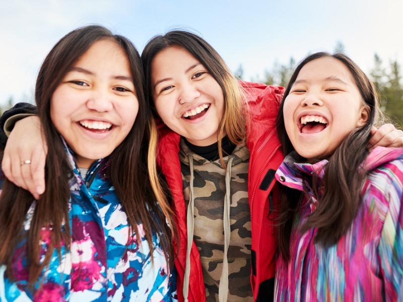 Trois jeunes autochtones souriantes sur un fonds hivernal.