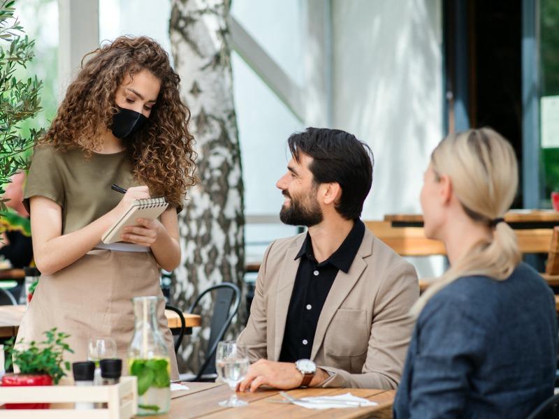 Une serveuse portant un masque, prenant la commande de deux clients.