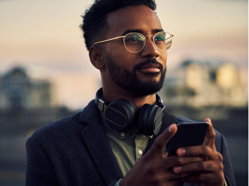 Un homme avec des écouteurs autour du cou qui regarde au loin, son téléphone dans les mains.