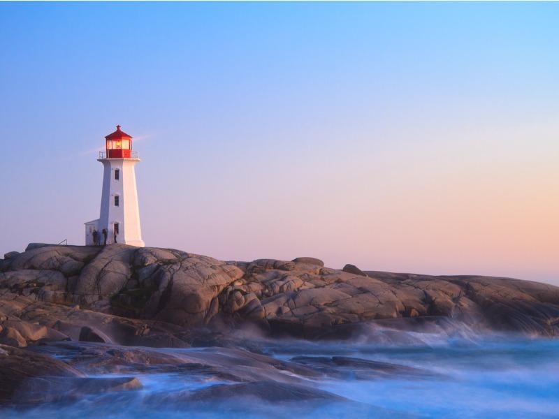 Un phare allumé au soleil levant.